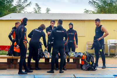 Divers in different types of SCUBA Wetsuits